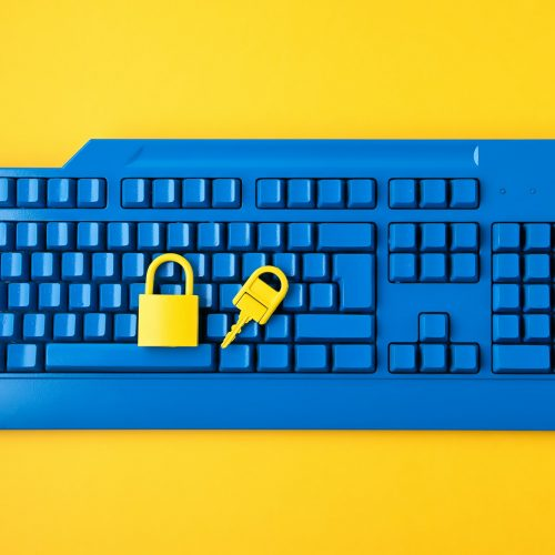 Cyber data and information security idea. Yellow padlock and key and blue keyboard. Computer