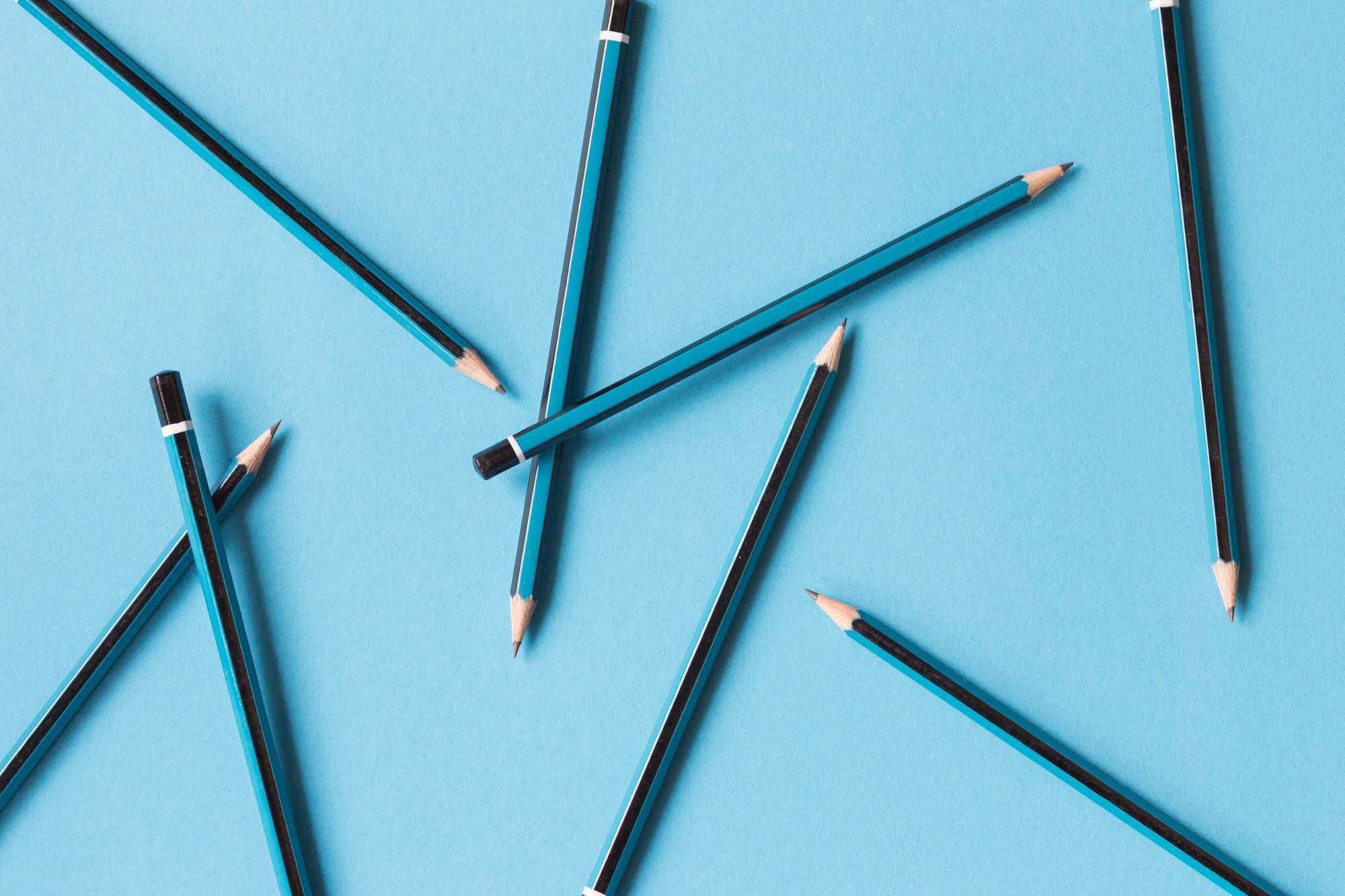 Blue and black pencils on blue background abstract